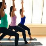 yogis_doing_warrior_pose_in_yoga_class